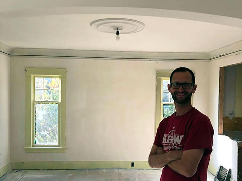 Homeowner with new ceiling medallion after all plaster repairs were completed.