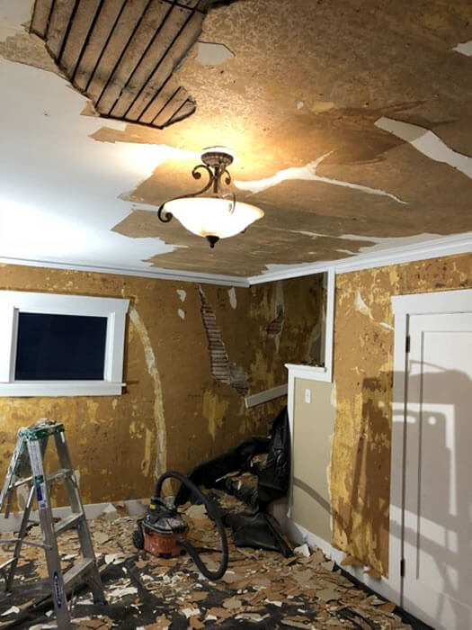 Removing damaged lath and plaster from living room walls, ceiling, and stairway.