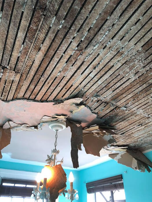 Removing loose and water damaged lath and plaster from ceiling.