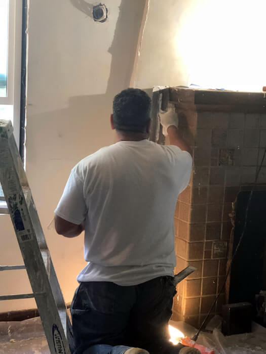 Repairing damage around the fireplace.