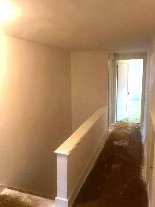 Stairway and second floor walls and ceiling after plaster was repaired and skimmed.